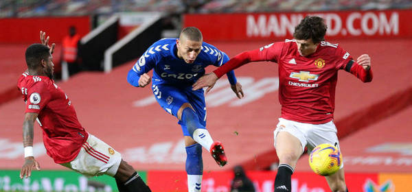 MANCHESTER, ENGLAND - FEBRUARY 06: Richarlison of Everton shoots under pressure from Fred and Victor Lindeloef of Manchester United during the Premier League match between Manchester United and Everton at Old Trafford on February 06, 2021 in Manchester, England. Sporting stadiums around the UK remain under strict restrictions due to the Coronavirus Pandemic as Government social distancing laws prohibit fans inside venues resulting in games being played behind closed doors. (Photo by Alex Pantling/Getty Images)