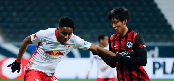 FRANKFURT AM MAIN, GERMANY - NOVEMBER 21: Christopher Nkunku (L) of Leipzig is challenged by Daichi Kamada of Frankfurt  during the Bundesliga match between Eintracht Frankfurt and RB Leipzig at Deutsche Bank Park on November 21, 2020 in Frankfurt am Main, Germany. Football Stadiums around Europe remain empty due to the Coronavirus Pandemic as Government social distancing laws prohibit fans inside venues resulting in fixtures being played behind closed doors. (Photo by Ronald Wittek - Pool/Getty Images)